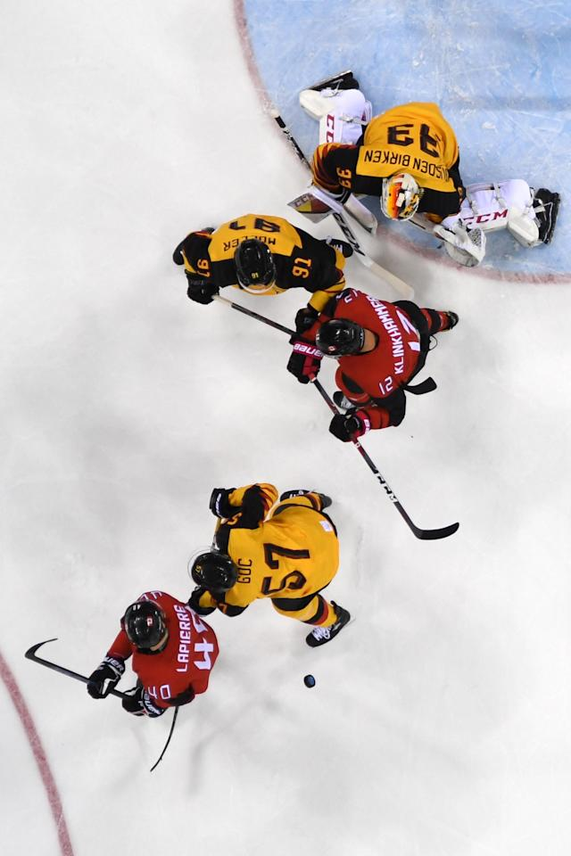 <p>Germany's Danny aus den Birken (top) watches a play in the Men's Ice Hockey semi-final's match between Canada and Germany during the PyeongChang 2018 Winter Olympic Games at the Gangneung Hockey Centre on February 23, 2018.<br> (Photo by Kirill Kudryavtsev/AFP/Getty Images) </p>