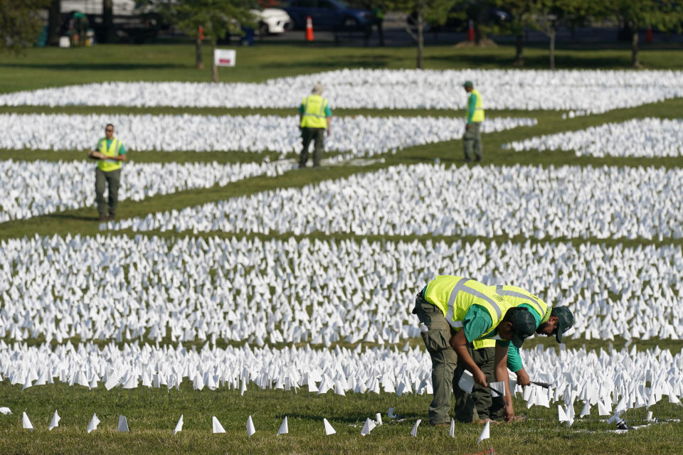 """Workers plant white flags as part of artist Suzanne Brennan Firstenberg's temporary art installation, """"In America: Remember,"""" in remembrance of Americans who have died of COVID-19, on the National Mall in Washington, Wednesday, Sept. 15, 2021. The installation will consist of more than 630,000 flags when completed. (AP Photo/Patrick Semansky)"""
