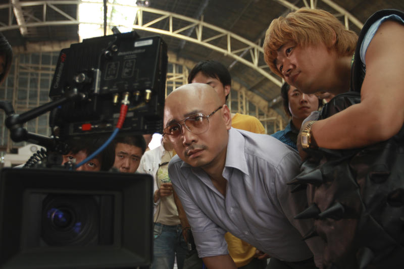 "In this publicity image released by Pegasus Motion Pictures, ""Lost in Thailand"" director, writer and star Xu Zheng, center, checks a monitor with his co-star Wang Baoqiang, right. The director of China's biggest box-office hit, says ""Lost in Thailand"" succeeded by showing a rarely seen subject: modern Chinese life. The historical epic, fantasy, action and thriller genres have long filled China's domestic movie screens. But ""Lost in Thailand"" was a low-budget and light-hearted road-trip tale about an ambitious executive who goes to Thailand to get his boss's approval for a business deal. Along the way he's pursued by a rival co-worker and encounters a wacky tourist who helps him rethink his priorities. (AP Photo/Pegasus Motion Pictures)"
