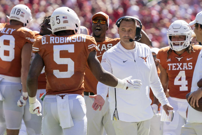 Texas head coach Steve Sarkisian congratulates running back Bijan Robinson (5) after a long run by Robinson during the first half of an NCAA college football game against Oklahoma at the Cotton Bowl, Saturday, Oct. 9, 2021, in Dallas. (AP Photo/Jeffrey McWhorter)