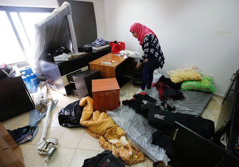 A Palestinian woman inspects the damage at the Palestine Today television offices after it had been raided by Israeli forces overnight on March 11, 2016, in the West Bank city of Ramallah (AFP Photo/Abbas Momani)