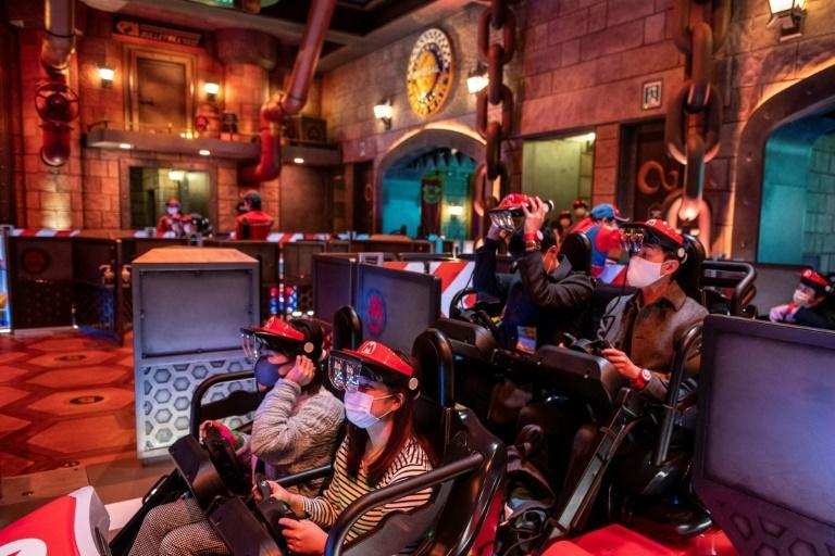 Augmented reality goggles attached to a plastic red visor are used in the 'Mario Kart' ride