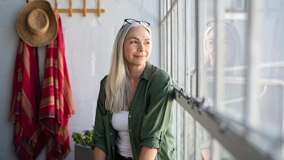 Smiling mature woman looking outside window.