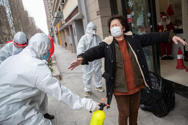 A woman who has recovered from the COVID-19 is disinfected by volunteers as she arrives at a hotel for a 14-day quarantine (AFP via Getty Images)