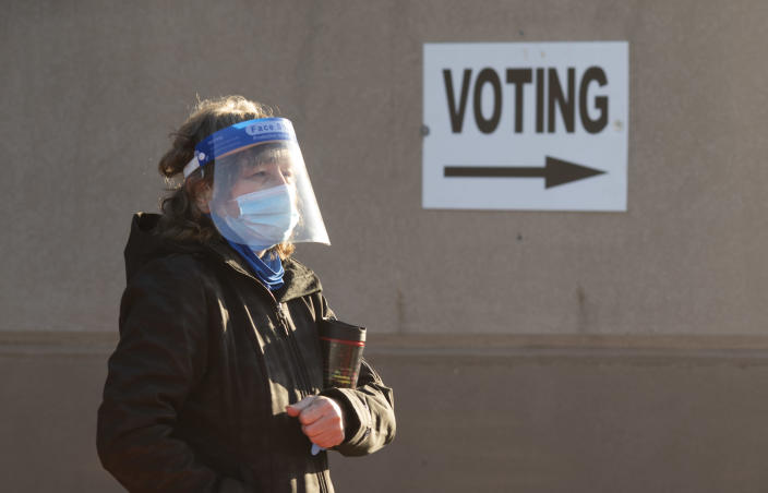 COLUMBUS, OH - OCTOBER 06: An early voter, wearing a mask and a face shield, stands in line waiting to register for early voting outside of the Franklin County Board of Elections Office on October 6, 2020 in Columbus, Ohio. Ohio allows early voting 28 days before the election which occurs on November 3rd of this year. (Photo by Ty Wright/Getty Images)
