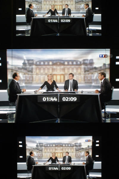 """A wall screen shows the televised debate between Socialist Party candidate for the presidential election Francois Hollande and current President and conservative rival for re-election, Nicolas Sarkozy, at the TF1 television studio, in Boulogne-Billancourt, outside Paris, Wednesday, May 2, 2012. The prime-time debate between conservative incumbent Sarkozy and his leftist challenger Hollande is billed in newspaper headlines Wednesday as """"The Last Duel"""" and """"The Final Confrontation,"""" providing a sense of suspense in a campaign that, if polls are right, has lacked it from the beginning. (AP Photo/Thibault Camus)"""