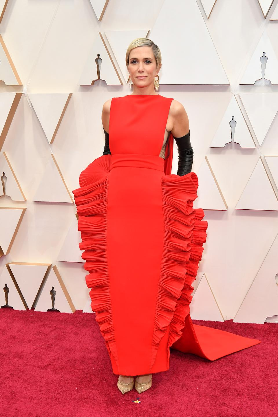 """The """"Bridesmaids"""" star and """"Saturday Night Live"""" alum opted for a high fashion look in a bold red gown with ruffled detailing."""