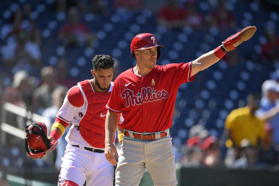 Philadelphia Phillies' J.T. Realmuto, right, gestures after he slid home to score against Washington Nationals catcher Keibert Ruiz, left, on a double by Andrew McCutchen during the sixth inning of a baseball game, Thursday, Sept. 2, 2021, in Washington. (AP Photo/Nick Wass)