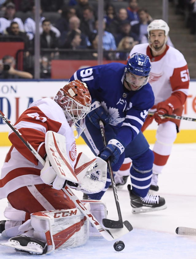 Toronto Maple Leafs center John Tavares (91) is stopped by Detroit Red Wings goaltender Jonathan Bernier (45) as Red Wings defenseman Jonathan Ericsson (52) watches during the first period of an NHL hockey game Thursday, Dec 6, 2018, in Toronto. (Nathan Denette/The Canadian Press via AP)