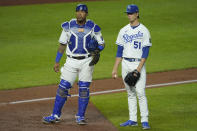 Kansas City Royals starting pitcher Brady Singer and catcher Salvador Perez wait while a play is reviewed during the sixth inning of a baseball game against the Cleveland Indians Wednesday, May 5, 2021, in Kansas City, Mo. (AP Photo/Charlie Riedel)