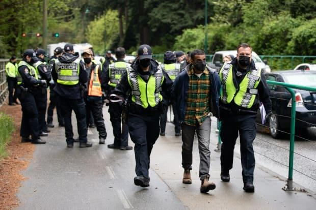 Climate change activist Zain Haq is arrested while blocking the sidewalk along Lions Gate Bridge Road in Vancouver, B.C., on Monday, May 3, 2021.