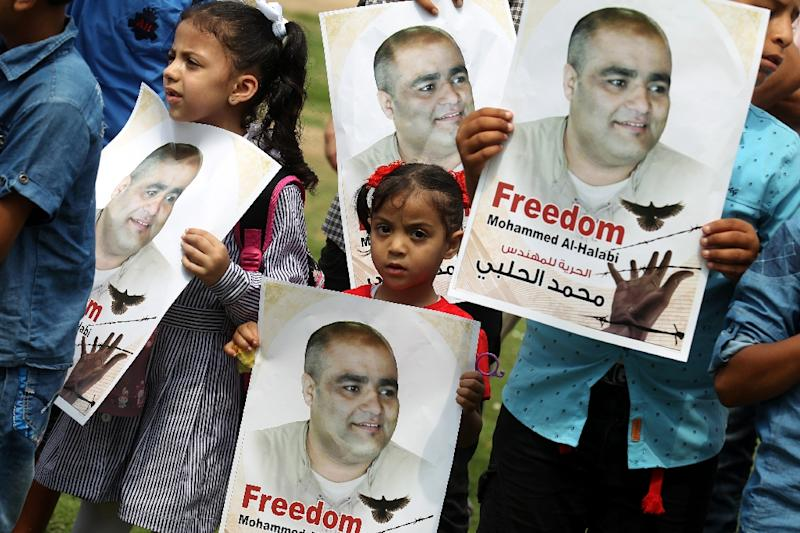 Palestinian children hold posters of Mohammed Halabi, the Gaza director of World Vision, during a protest to support him in the southern Gaza Strip on August 29, 2016