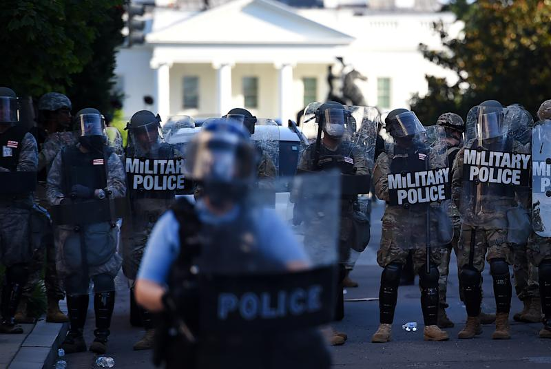 Military Police members hold a perimeter near the White House as demonstrators gather to protest the killing of George Floyd on June 1, 2020 in Washington, DC. - Police fired tear gas outside the White House late Sunday as anti-racism protestors again took to the streets to voice fury at police brutality, and major US cities were put under curfew to suppress rioting.With the Trump administration branding instigators of six nights of rioting as domestic terrorists, there were more confrontations between protestors and police and fresh outbreaks of looting. Local US leaders appealed to citizens to give constructive outlet to their rage over the death of an unarmed black man in Minneapolis, while night-time curfews were imposed in cities including Washington, Los Angeles and Houston. (Photo by Olivier DOULIERY / AFP) (Photo by OLIVIER DOULIERY/AFP via Getty Images)