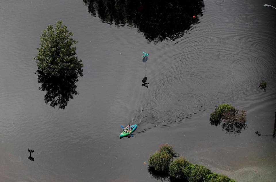 A man paddles a kayak in a flooded neighborhood in Fayetteville.