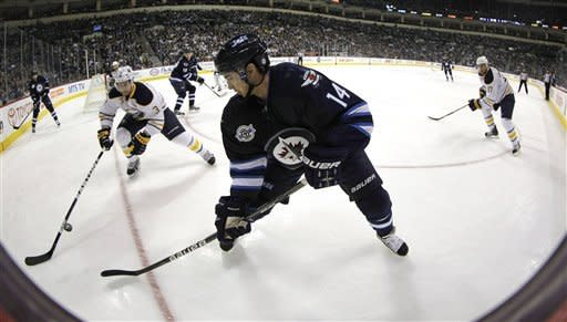 Winnipeg Jets' Tim Stapleton (14) flips a pass over the stick of Buffalo Sabres' Jordan Leopold (3) during the second period of an NHL hockey game in Winnipeg, Manitoba, Monday, March 5, 2012. (AP Photo/The Canadian Press, Trevor Hagan)