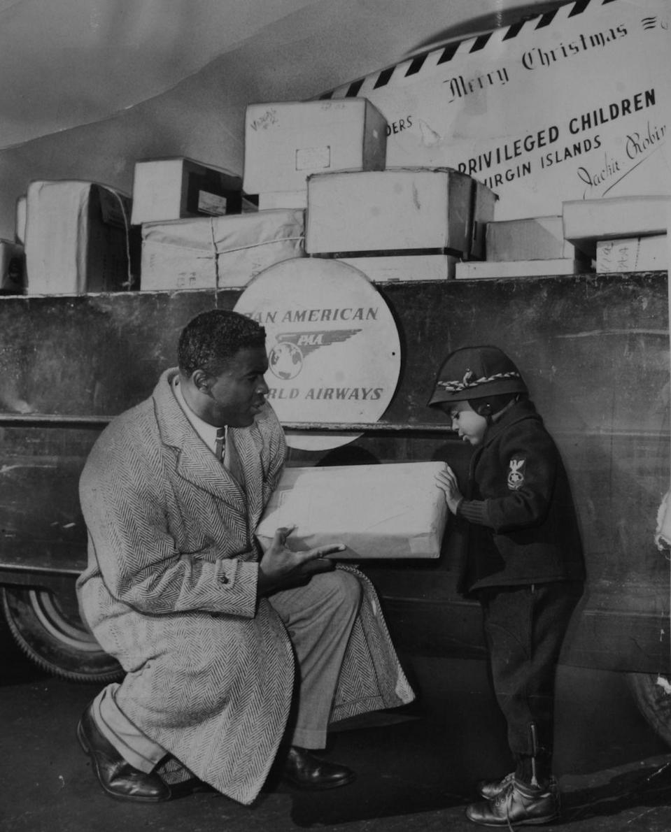 <p>The Brooklyn Dodgers baseball player and his son prepare presents for children who are less fortunate during the holiday season in 1950. </p>