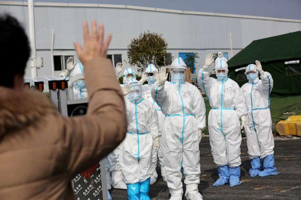 PHOTO: Medical personnel in protective suits wave hands to a patient who is discharged from the Leishenshan Hospital after recovering from the novel coronavirus, in Wuhan, China, March 1, 2020. (China Daily/Reuters)