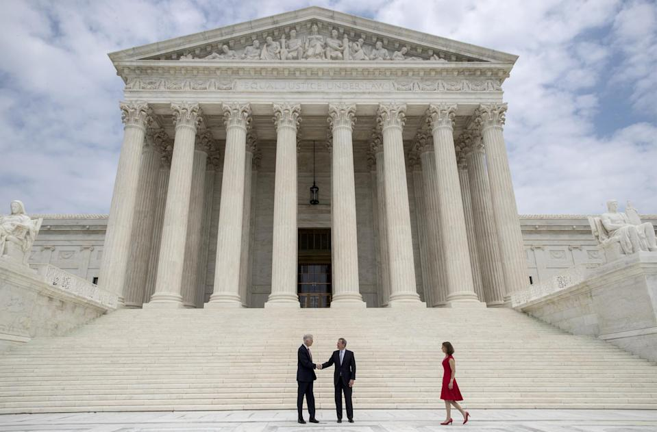 Associate Supreme Court Justice Neil Gorsuch shakes hands with Chief Justice John Roberts (AP)