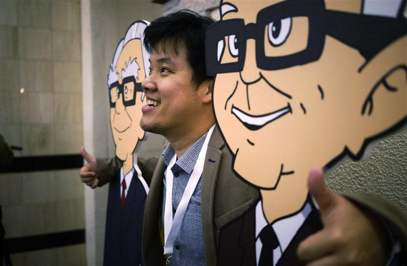 A Berkshire Hathaway shareholder poses with caricatures of CEO Buffett and Vice-Chairman Munger at a welcome cocktail reception in Omaha