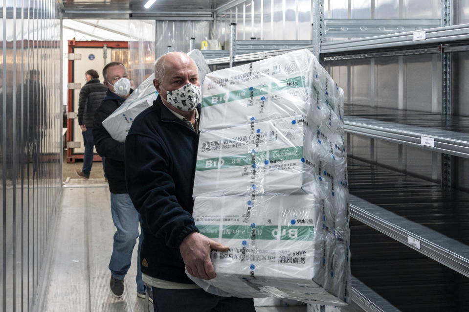 Employees unload the newly arrived coronavirus vaccines from Chinese pharmaceutical company Sinopharm at the logistics base set up to in the parking lot of the government office in the 13th district of Budapest, Hungary, March 3, 2021. (Zsolt Szigetvary/MTI via AP)