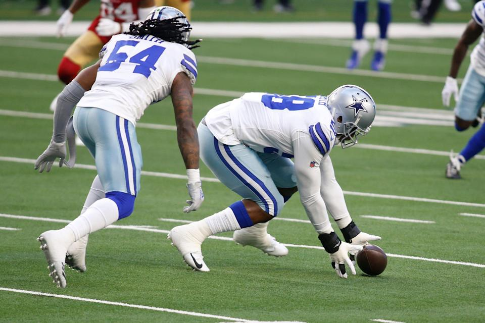Dallas Cowboys defensive end Aldon Smith (58) picks up a fumble against the San Francisco 49ers in the first quarter at AT&T Stadium.