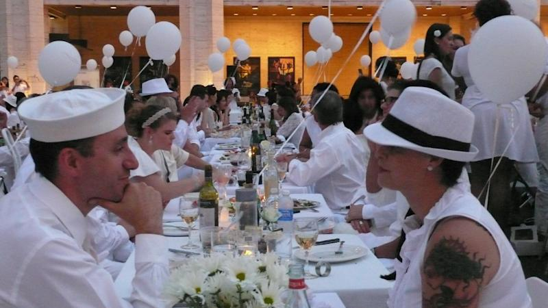 Matthew Karl Gale, left, from New York's borough of Brooklyn, and  Cassandra McCall, of San Francisco, sit at their outdoor table at Lincoln Center for the Performing Arts kin New York  as part of the Diner en Blanc flash-mob dinner  Aug. 20, 2012.  On Monday night 3,000 people all dressed in white, descended on the Lincoln Center for the Performing Arts.  (AP Photo/Verena Dobnik)