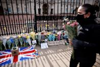 "<p>Flowers are placed outside Buckingham Palace alongside a sign that reads ""Thank you Philip"" on April 9. </p>"