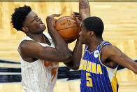 Orlando Magic center Mo Bamba, left, tires to get off a shot against Indiana Pacers guard Edmond Sumner (5) during the second half of an NBA basketball game, Sunday, April 25, 2021, in Orlando, Fla. (AP Photo/John Raoux)