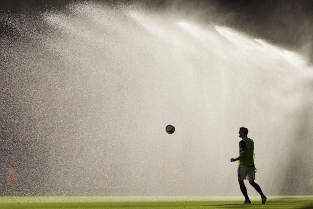 Southampton's Jos Hooiveld warms up at half time as the pitch is watered during his team's English Premier League soccer match against Liverpool at Anfield Stadium, Liverpool, England, Saturday Sept. 21, 2013. (AP Photo/Jon Super)