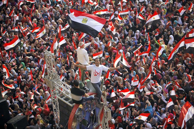 "Opponents of Egypt's Islamist President Mohammed Morsi shout slogans and wave a national flags in Tahrir Square in Cairo, Egypt, Wednesday, July 3, 2013. Arabic reads, "" leave."" The deadline on the military's ultimatum to President Mohammed Morsi has expired, with 48 hours passing since the time it was issued. Giant cheering crowds of Morsi's opponents have been gathered in Cairo's Tahrir Square and other locations nationwide, waving flags furiously in expection that the military will act to remove the Islamist president after the deadline ends. (AP Photo/Amr Nabil)"