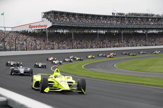 FILE - In this May 26, 2019, file photo, Simon Pagenaud, of France, leads the field through the first turn on the start of the Indianapolis 500 IndyCar auto race at Indianapolis Motor Speedway, in Indianapolis. It is finally May and acceptable to declare this a crummy year for Roger Penske to have purchased Indianapolis Motor Speedway. The iconic track was scheduled to open this week for racing, but everything has been put on hold, including the Indianapolis 500, because of the coronavirus pandemic. (AP Photo/Darron Cummings, File)