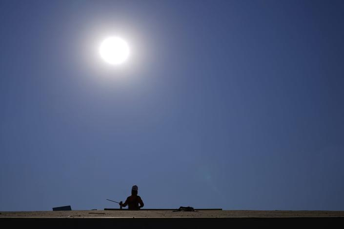 A roofer works on a new roof in a housing development while the sun beats down on him as the heat wave continues Thursday, June 17, 2021, in Phoenix. (AP Photo/Ross D. Franklin)