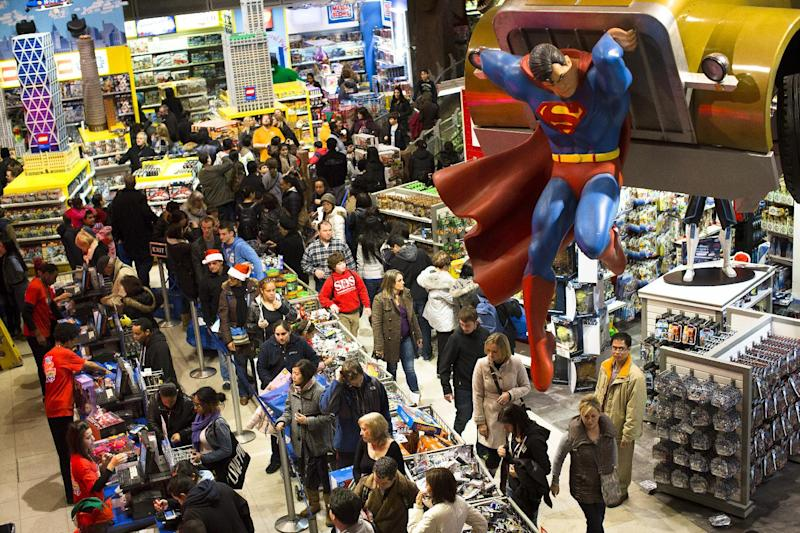 FILE - In this Thursday, Nov. 22, 2012, file photo, shoppers wait on a check-out line in the Times Square Toys-R-Us store after doors were opened to the public at 8 p.m., in New York. U.S. shoppers hit stores and websites at record numbers over the four-day Thanksgiving weekend, according to a survey released by the National Retail Federation on Sunday. They were attracted by retailers' efforts to make shopping easier, including opening stores on Thanksgiving evening, updating mobile shopping applications for smartphones and tablets, and expanding shipping and layaway options. (AP Photo/John Minchillo)