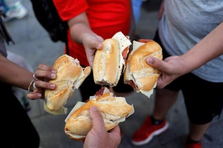 FILE PHOTO: Tourists show sadwhiches with ham and cheese bought in a bar in Madrid