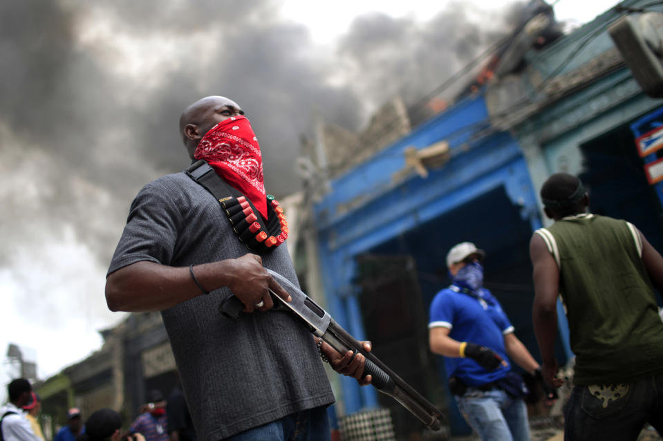 <p>A private security guard stands outside a burning store in downtown Port-au-Prince, Haiti, Jan.19, 2010. (Photo: Carlos Barria/Reuters) </p>
