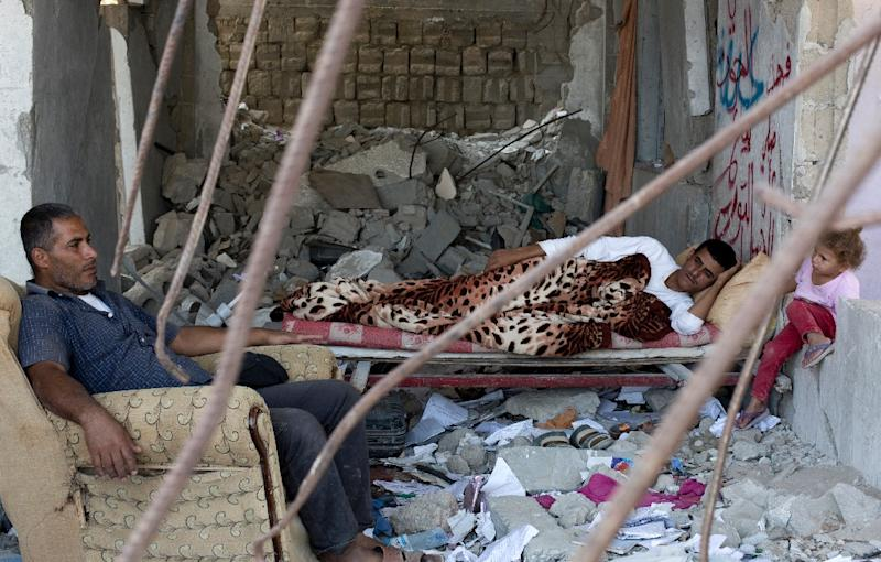 A Palestinian family rests on July 2, 2015, in the rubble of a building that was destroyed during the 50-day war between Israel and Hamas' militants in the summer of 2014, in the al-Shejaeiya neighbourhood, east of Gaza City (AFP Photo/Mohammed Abed)