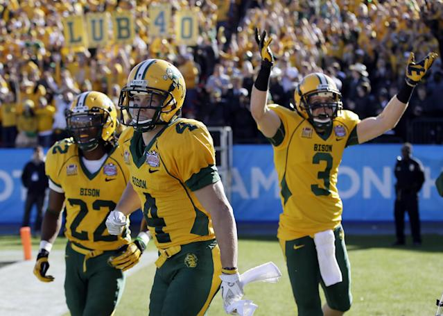 North Dakota State's Sam Ojuri, left, Ryan Smith (4), and Trevor Gebhart (3) celebrate a touchdown by Smith in the first half of the FCS championship NCAA college football game against Towson, Saturday, Jan. 4, 2014, in Frisco, Texas. (AP Photo/Tony Gutierrez)