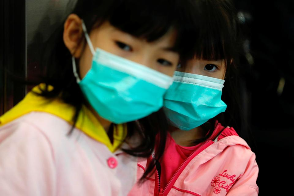 Children wear masks to prevent an outbreak of a new coronavirus at the Hong Kong West Kowloon High Speed Train Station, in Hong Kong, China January 23, 2020. REUTERS/Tyrone Siu