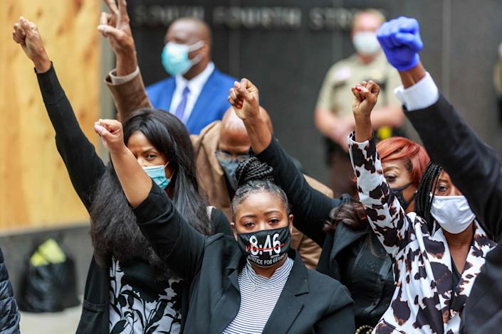 George Floyd's family raise their hands as attorney Ben Crump (out of frame) speaks at a press conference outside the family justice center after a court hearing on the murder of George Floyd on Sept. 11, 2020, in Minneapolis, Minnesota. Four police officers accused of contributing to the death of George Floyd, the 46-year-old African-American man whose death in May sparked nationwide protests, appeared together in Minneapolis court for the first time that day.
