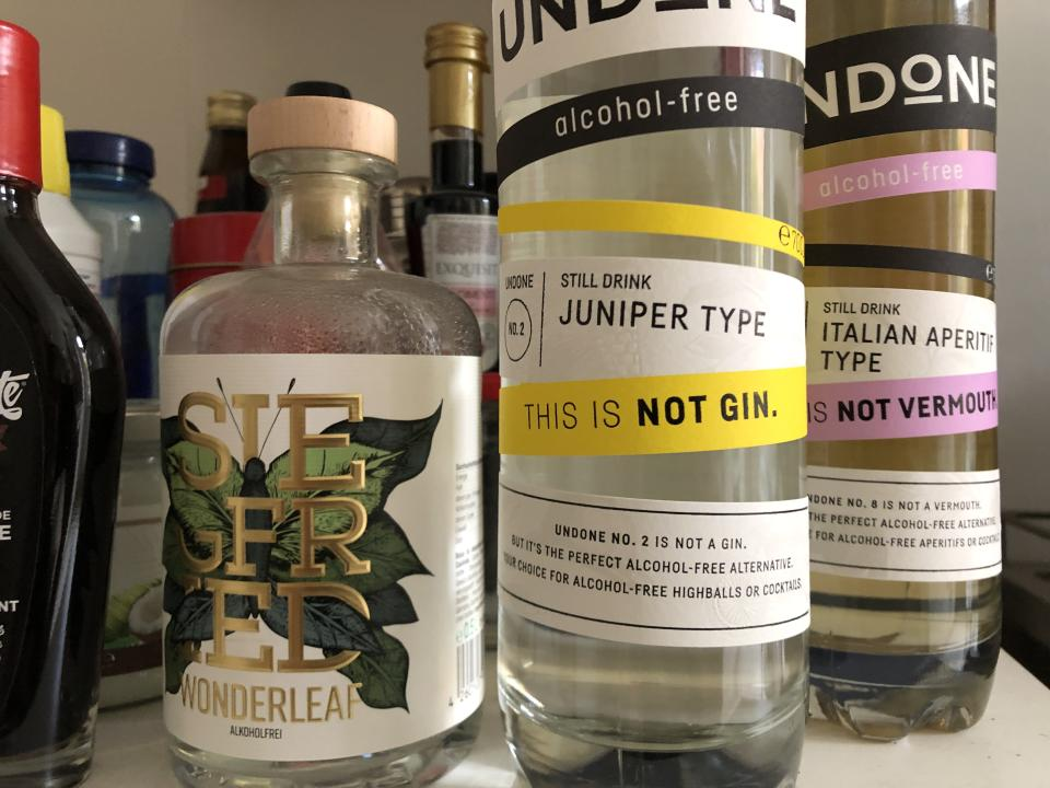 "24 September 2019, Berlin: A bottle of 'Wonderleaf' (l-r), non-alcoholic 'Gin' of the German trade mark Siegfried Rheinland Dry Gin, a bottle of 'Juniper Type' (juniper type) with the inscription 'This is not Gin' and a bottle of 'Italian Aperitif Type' with the inscription 'This is not Vermouth/kein Wermut' are on a shelf. Alcohol renunciation seems to be a trend. (to dpa-Korr ""This is not gin"": Alcohol renunciation without loss of taste?"") Photo: Gregor Tholl/dpa (Photo by Gregor Tholl/picture alliance via Getty Images)"
