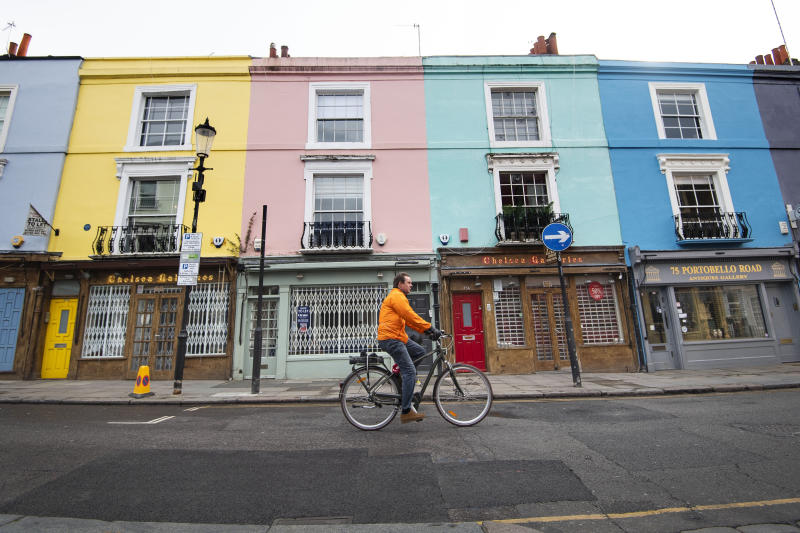 A cyclist rides past closed up shops on Portobello Road in West London as the UK continues in lockdown to help curb the spread of the coronavirus.