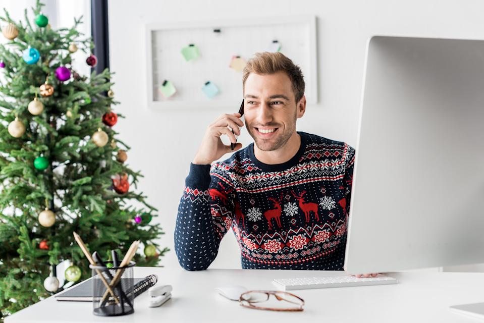 businessman in christmas sweater talking on smartphone in modern office