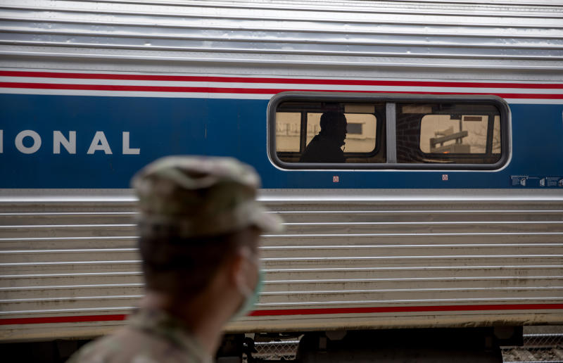 A soldier with the Rhode Island National Guard looks for passengers getting off a train from New York as it arrives Saturday, March 28, 2020, in Westerly, R.I. States are pulling back the welcome mat for travelers from the New York area, which is the epicenter of the country's coronavirus outbreak, and some say at least one state's measures are unconstitutional. Gov. Gina Raimondo ratcheted up the measures announcing she'll also order the state National Guard to go door-to-door in coastal communities starting this weekend to find out whether any of the home's residents have recently arrived from New York and inform them of the quarantine order. (AP Photo/David Goldman)