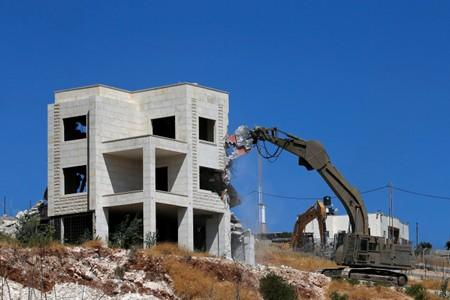 Israeli machinery demolishes a Palestinian house in the village of Sur Baher which sits on either side of the Israeli barrier in East Jerusalem and the Israeli-occupied West Bank