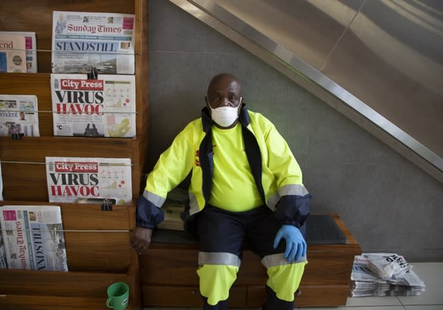 A masked newspaper seller waits to make a sale in Johannesburg