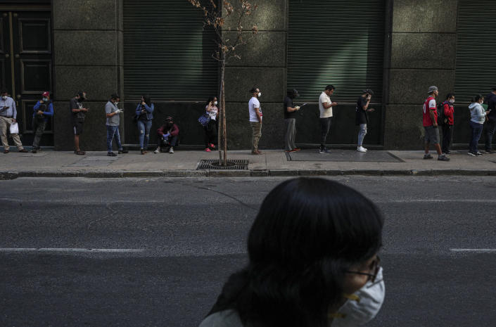 People wait in line to collect unemployment insurance, many of them affected by the economic crisis triggered by the spread of the new coronavirus, in downtown Santiago, Chile, Monday, April 6, 2020. (AP Photo/Esteban Felix)
