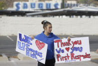 Student Sayla David, 12, holds thank you signs for first responders outside the Saugus High School in Santa Clarita, Calif., Friday, Nov. 15, 2019. A homicide official says that investigators did not find a diary, manifesto or note belonging to the boy who killed two people outside his Southern California high school on his 16th birthday. No motive or rationale has been established yet in the Thursday morning shooting at Saugus High School in the Los Angeles suburb of Santa Clarita. (AP Photo/Damian Dovarganes)