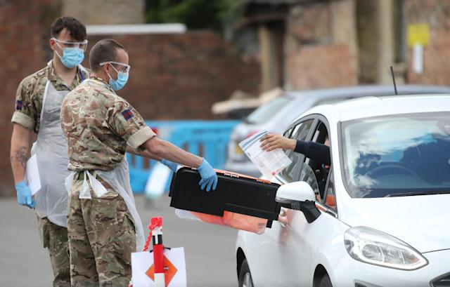 A driver wearing PPE hands a swab test to soldiers helping at a pop-up COVID-19 drive-through testing centre in Dalston, Hackney, east London. (PA)