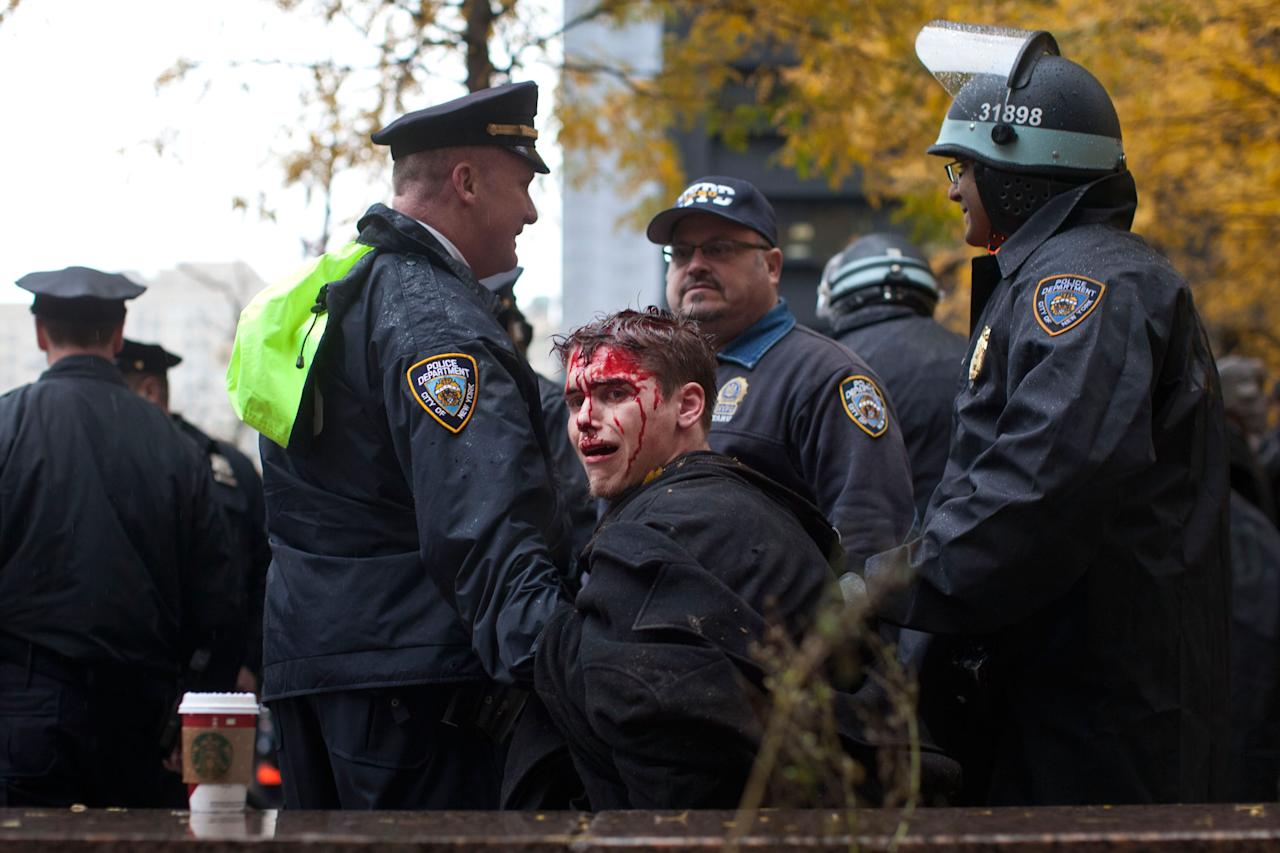 NEW YORK, NY - NOVEMBER 17:  A man who identifed himself as Brendan Watts is seen with blood on his face while surrounded by three police officers in Zuccotti Park on November 17, 2011 in New York City. A fight broke out between protestors affiliated with Occupy Wall Street and police, in which Watts was injured.  (Photo by Andrew Burton/Getty Images)