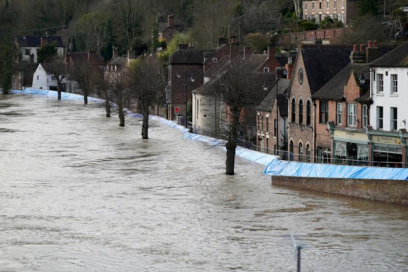 Buildings are seen behind temporary flood barriers that are overwhelmed by water: Getty Images